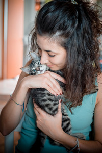 woman hugging cat at home
