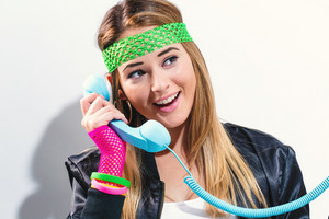 Woman in 1980's fashion with old fashioned phone on a white background