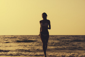 Woman in a swimsuit runs out of the water on the beach. Silhouette of a woman on the beach against the backdrop of the water during sunset.