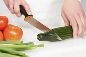 Woman in a white kitchen chopping a cucumber to a salad with a knife.