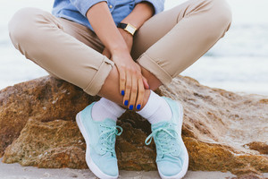 Woman in beige pants and a denim shirt and turquoise sneakers sitting on a rock by the sea. Shirt sleeves rolled up, watch on his arm, a blue manicure. Arms and legs crossed. Close-up, outdoors.