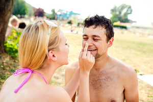 Woman in bikini putting sunscreen on nose of  a man. Sunbathing in summer.