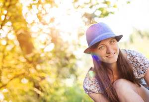 Woman in blue hat in summer sunny nature.