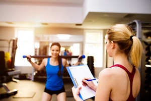 Woman in blue singlet exercising squats with bar in a gym  with her personal trainer writing into exercise plan on clipboard
