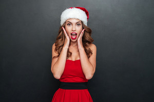 Woman in christmas dress very surprised. Hands to face. Black background