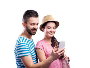 Woman in hat and a hipster man in summer clothes with smartphone, taking selfie, making funny face. Studio shot on white background, isolated.