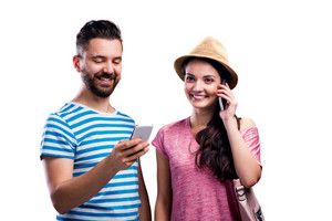 Woman in hat and a hipster man in summer clothes with smartphones, making a phone call, writing a text message. Studio shot on white background, isolated.