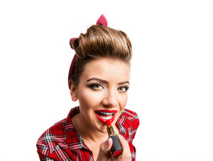 Woman in red checked shirt with pin-up make-up and hairstyle applying lipstick. Studio shot on white background
