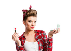 Woman in red checked shirt with pin-up make-up and hairstyle holdin a mirror and applying lipstick. Studio shot on white background
