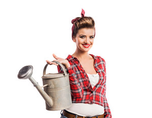 Woman in red checked shirt with pin-up make-up and hairstyle holding metal watering can. Studio shot on white background