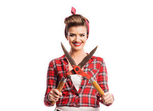 Woman in red checked shirt with pin-up make-up and hairstyle holding pruning shears. Studio shot on white background