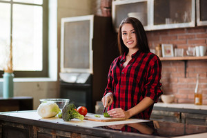 Woman in red shirt cooking in kitchen and looking at camera. Side view