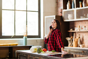 Woman in red shirt standing at the table and talking on phone in kitchen. Side view