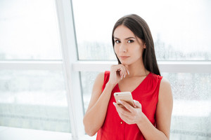 Woman in red shirt with phone standing near the window in office and looking at camera