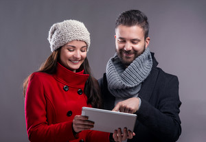 Woman in red winter coat and a hipster man with knitted scarf with tablet. Studio shot on gray background.