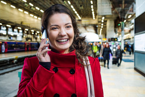 Woman in red winter coat waiting on train station talking on the phone