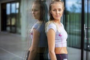Woman In Sportswear Listening Music Against Glass Wall