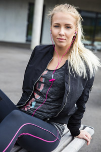 Woman In Sportswear Listening Music While Sitting On Bench