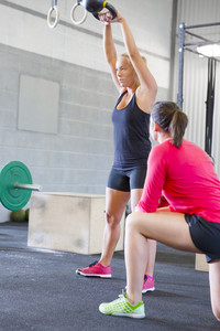 Woman lift kettlebells weights with personal trainer