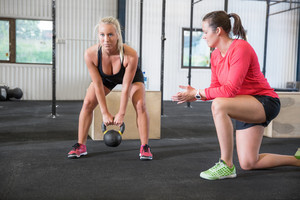 Woman lifts kettlebell weights with personal trainer
