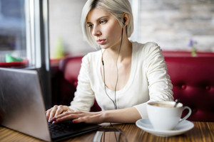 Woman Listening Music While Working On Laptop In Cafe
