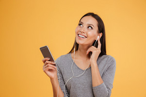 Woman listening to music at phone in studio. isolated orange background
