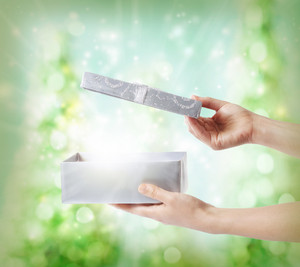 Woman opening a silver gift box on a green holiday lights background
