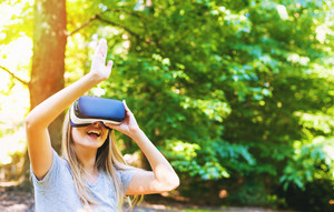 Woman playing with a virtual reality headset outside