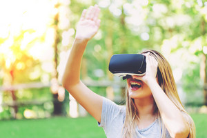 Woman playing with virtual reality headset outside