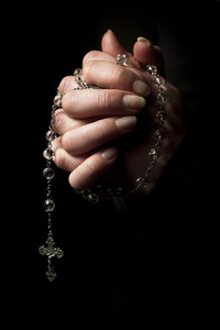Woman praying to God with hands folded. Holdig a cross.