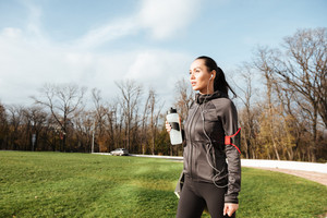 Woman pretty runner in warm clothes looking aside in autumn park while holding bottle of water