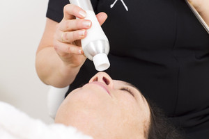 Woman receives face treatments at beauty clinic