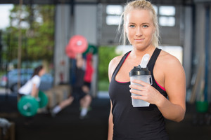 Woman rest and drinking water at fitness gym