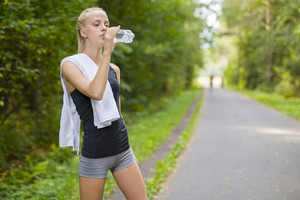 Woman runner drinking water after running