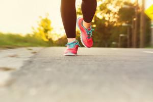 Woman runner jogging down an outdoor path at sunset