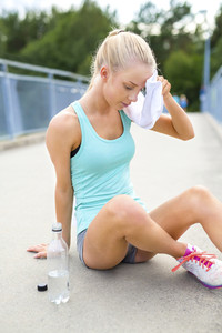 Woman runner sitting on the ground and takes a break