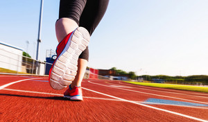 Woman running on a red athletic stadium track