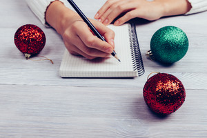 Woman sitting at desk and writing in a notebook with a pencil, lay next to Christmas decorations