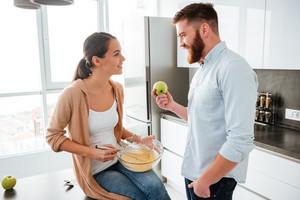 Woman sitting on table in kitchen with man. woman cooked. man with apple. eyes to eyes