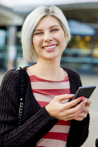 Woman Smiling While Using Smart Phone Outside Train Station