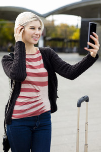 Woman Taking Selfie With Mobile Phone Outside Railroad Station
