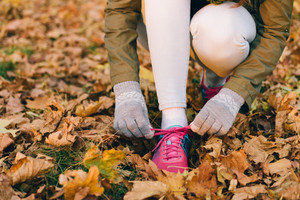 Woman tying shoelaces on sneakers during an autumn walk in the park. A woman dressed in a jacket, jeans, gloves and shoes.