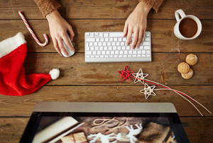 Woman typing at workplace with coffee, biscuits and Christmas symbols near by