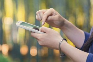 Woman using her white smartphone in the bamboo forest at sunset