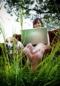 Woman using laptop on couch in sunny field in countryside