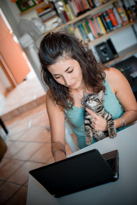 woman using notebook with cat at home