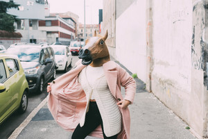 Woman wearing horse mask dancing outdoor in the city - strange, absurd, carnival concept