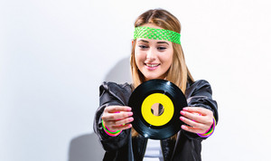 Woman with a vinyl record in 1980's fashion on a white background
