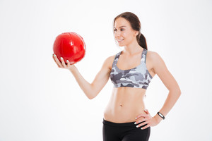 Woman with ball in studio. stands sideways. isolated white background