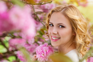 Woman with blond curly hair against pink tree in blossoom, spring nature